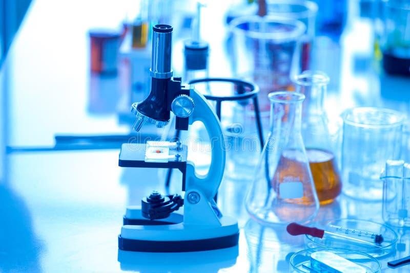 Tubes à essai de microscope et becher sur le fond bleu photographie stock