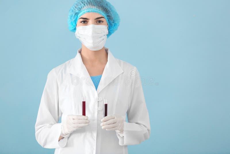 Tubes à essai de participation de technicien de laboratoire avec la prise de sang sur le fond de couleur photographie stock