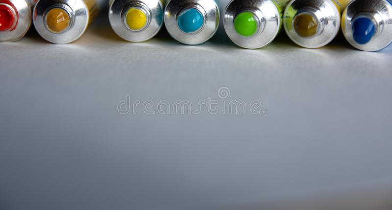 Tubes close-up with bright multi-colored watercolors blue, yellow, green shades. Good background for art publications.  stock photo