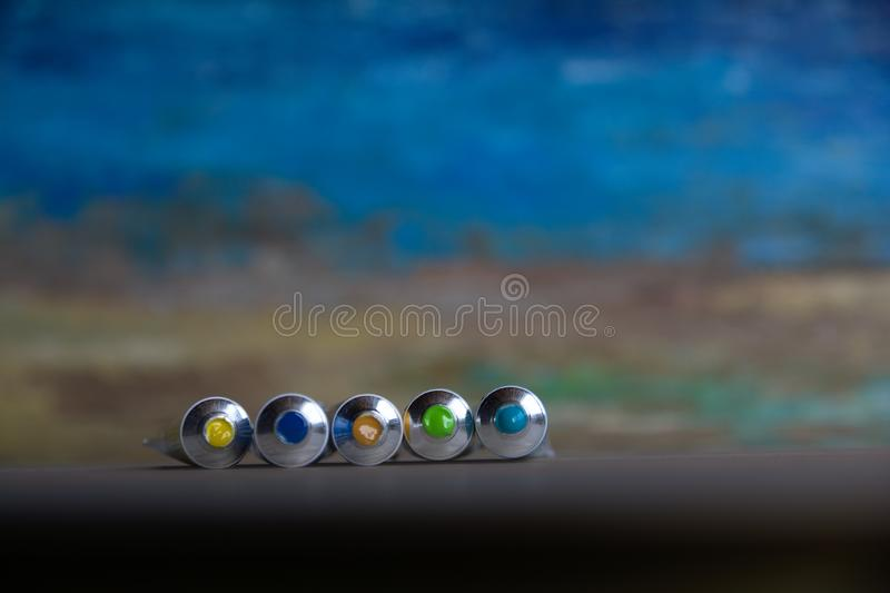 Tubes close-up with bright multi-colored watercolors blue, yellow, green shades. Good background for art publications.  royalty free stock image