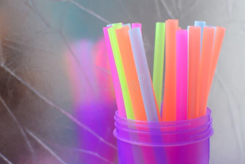 Tubes en plastique multicolores lumineux dans un verre pourpre translucide sur un fond argenté images libres de droits