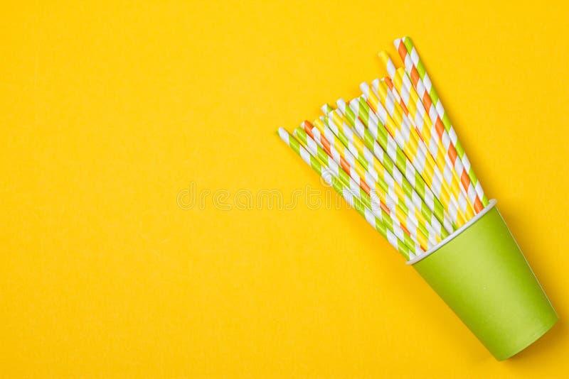 Tubes multicolores de cocktail dans la tasse jetable de Livre vert photo libre de droits