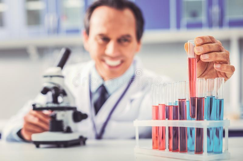 Glass tubes with different chemical substances standing near microscope stock images