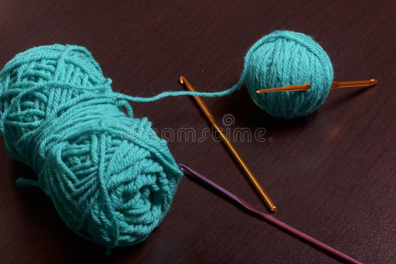 Tubes of thread for knitting emerald color and hooks for knitting on a dark background. royalty free stock photography