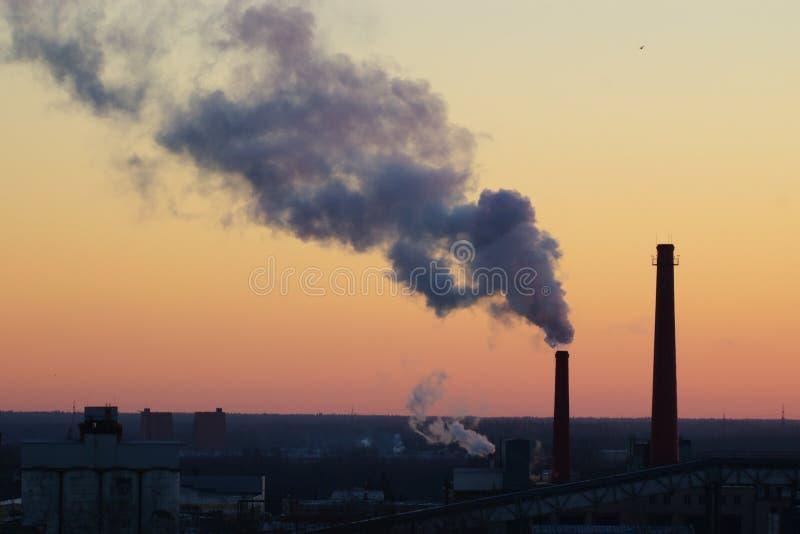 Tubi che inquinano in cielo di alba fotografia stock