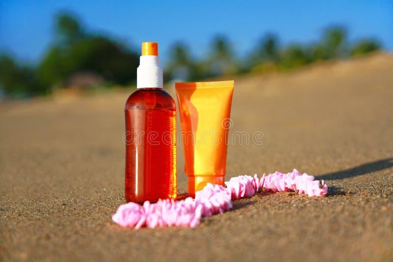 Tubi con sunblock e pane sulla sabbia sulla spiaggia fotografia stock