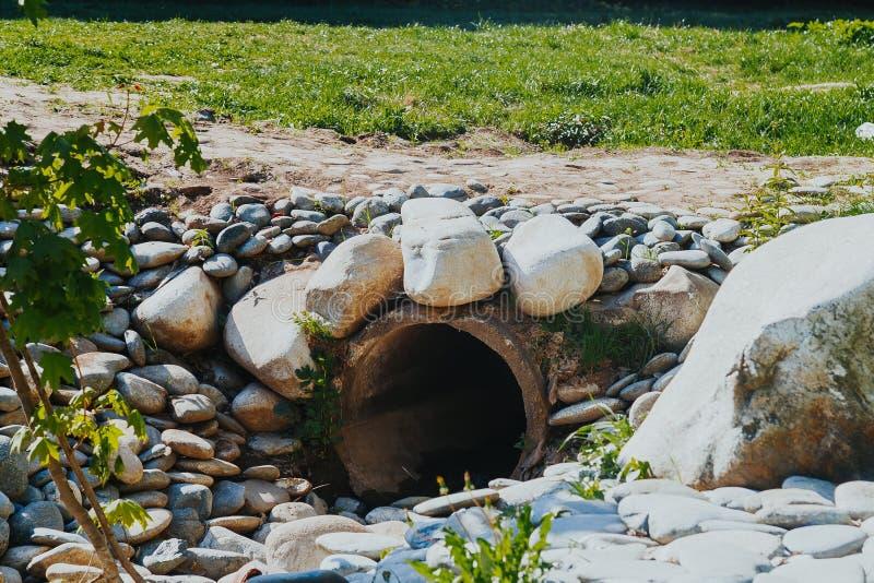 Tubi concreti di drenaggio per drenaggio naturale dell'acqua piovana fotografia stock libera da diritti