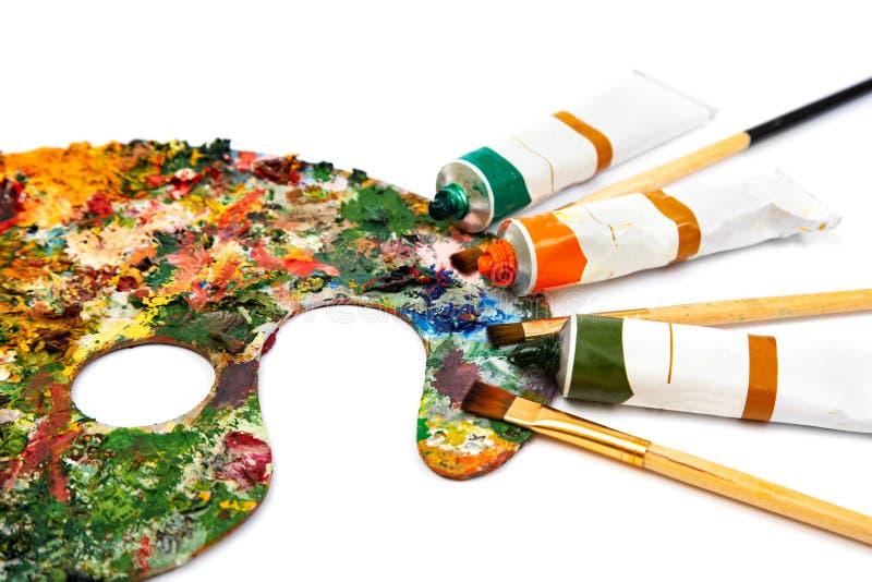 Tubi dei pennelli multicolori della pittura ad olio e dell'artista sul primo piano della tela Tavolozza con le pitture variopinte immagine stock libera da diritti