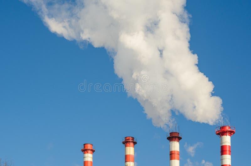 Tubi della pianta con fumo contro cielo blu fotografie stock