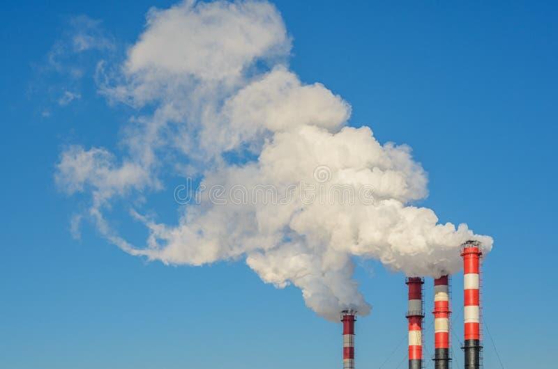 Tubi della pianta con fumo contro cielo blu fotografia stock libera da diritti