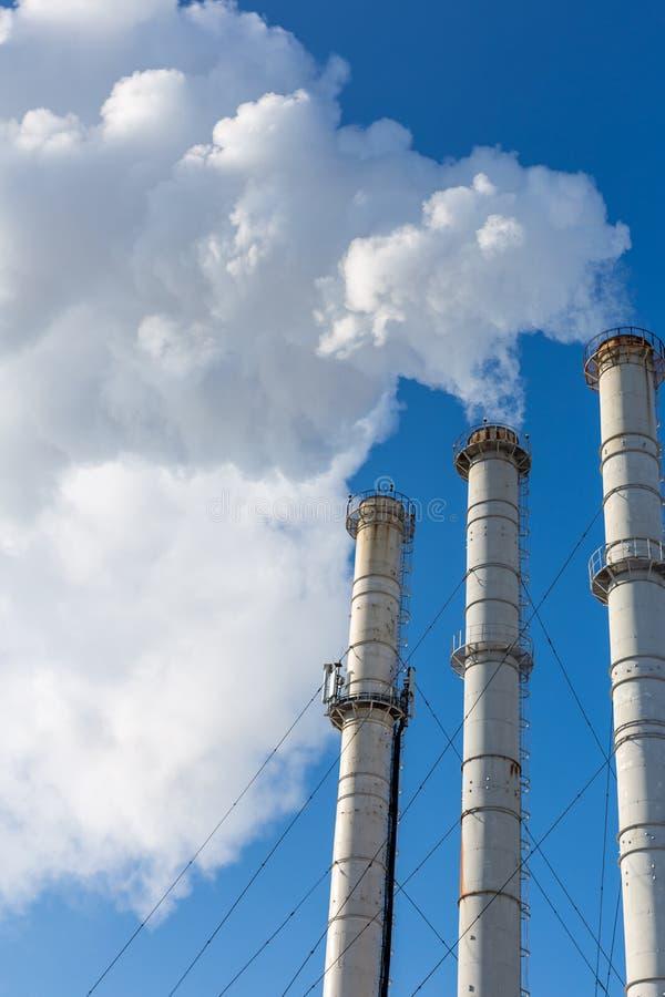 Tubi di fumo che fanno le nuvole contro il fondo del cielo blu Contaminazione dell'aria del diossido Inquinamento ambientale immagine stock