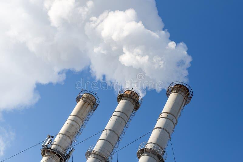 Tubi di fumo che fanno le nuvole contro il fondo del cielo blu Contaminazione dell'aria del diossido Inquinamento ambientale fotografia stock libera da diritti