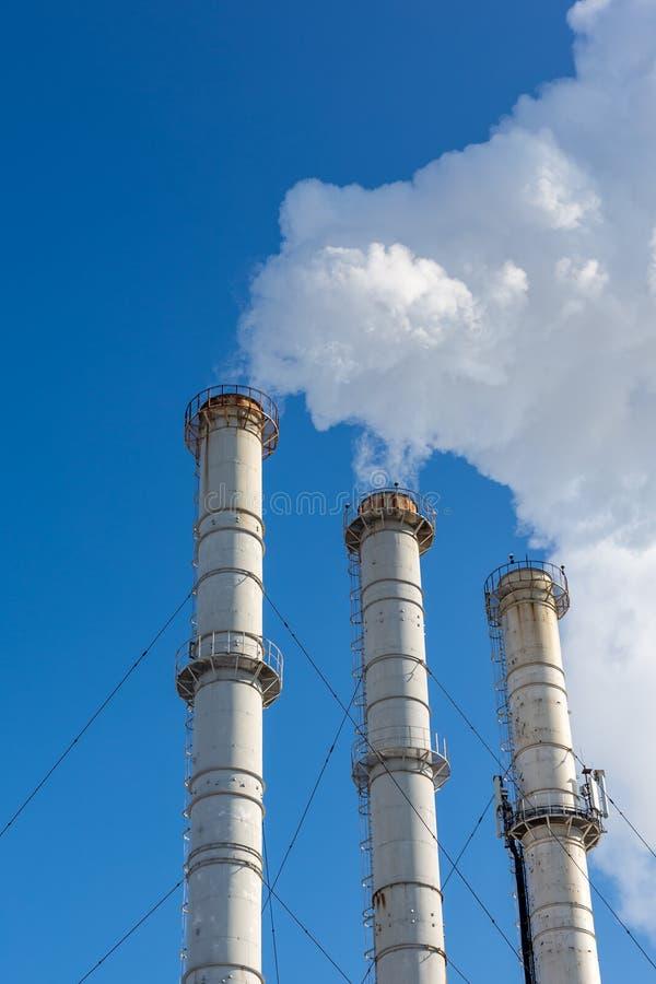 Tubi di fumo che fanno le nuvole contro il fondo del cielo blu Contaminazione dell'aria del diossido Inquinamento ambientale fotografie stock libere da diritti