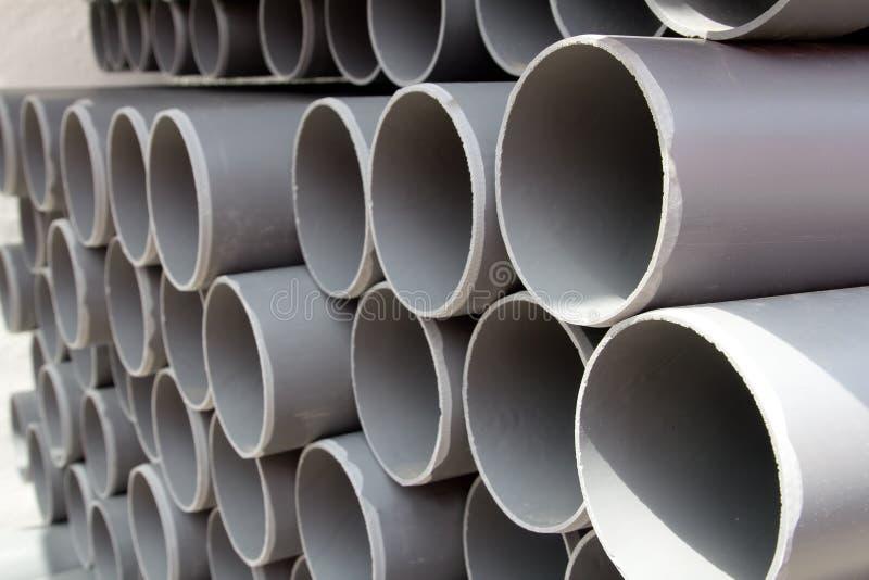 Tubi di plastica dei tubi grigi del PVC impilati nelle righe fotografia stock libera da diritti