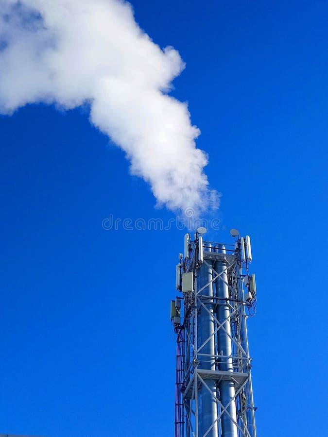 Tubi e fumo sui precedenti del cielo blu fotografia stock
