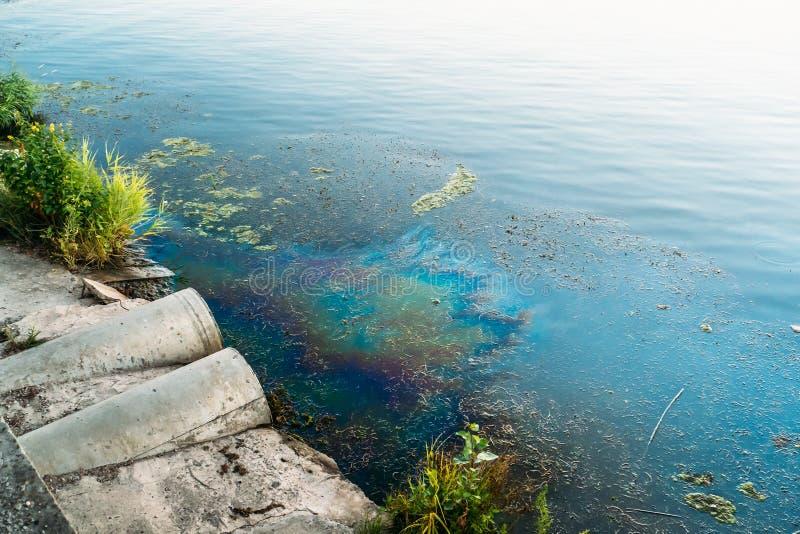 Tubi per fognatura alla riva, alla macchia di olio o al combustibile sulla superficie dell'acqua, inquinamento dai prodotti chimi fotografia stock libera da diritti