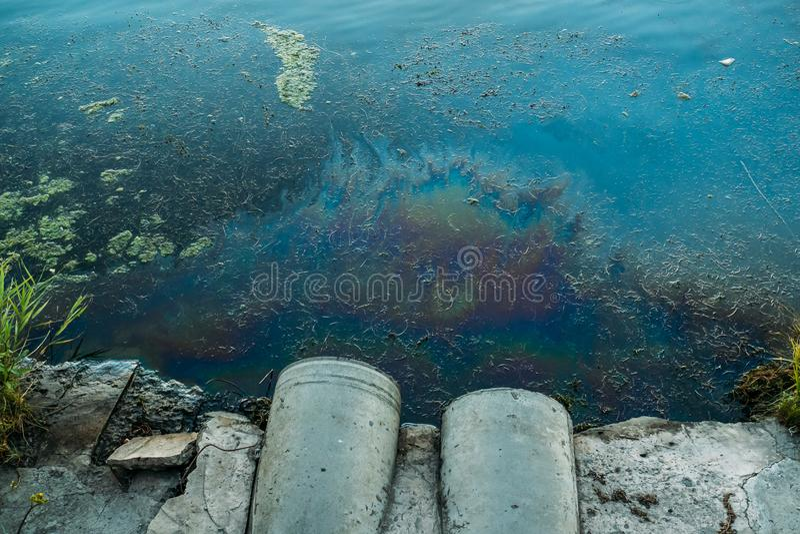 Tubi per fognatura alla riva, alla macchia di olio o al combustibile sulla superficie dell'acqua, inquinamento dai prodotti chimi immagini stock