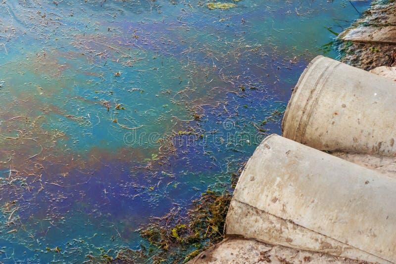 Tubi per fognatura alla riva, alla macchia di olio o al combustibile sulla superficie dell'acqua, inquinamento dai prodotti chimi fotografia stock