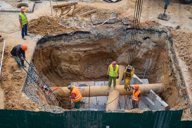 Tubi per fognatura di riparazione dei costruttori Lavorando con la gru fotografie stock