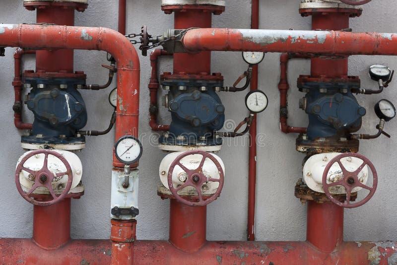 Tubi rossi con le valvole ed i manometri immagine stock libera da diritti