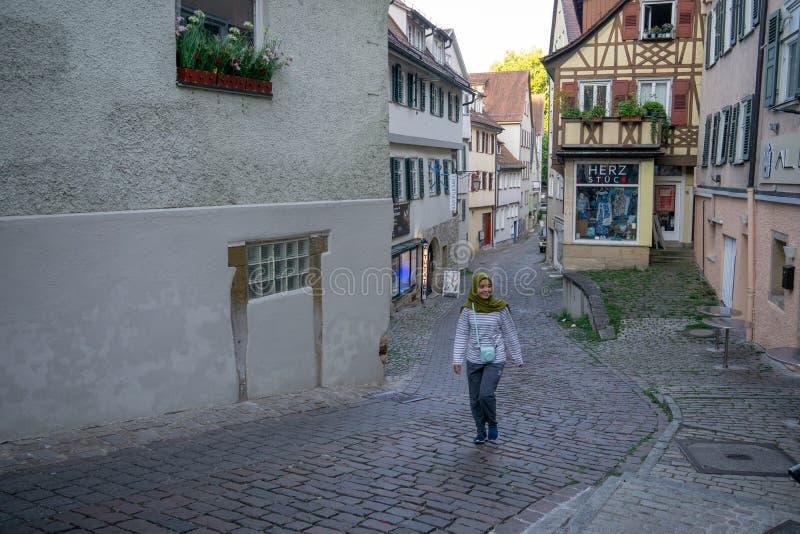 TUBINGEN/GERMANY- 30 DE JULHO DE 2019: Uma moça muçulmana que anda no trajeto perto das casas metade-suportadas velhas agradáveis foto de stock royalty free