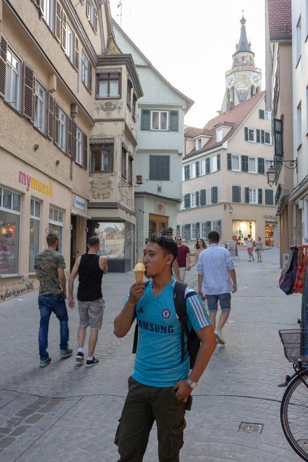 TUBINGEN/GERMANY- 31 DE JULIO DE 2018: un turista masculino de Asia está gozando del helado alrededor de la ciudad peatonal de Tu imagen de archivo libre de regalías
