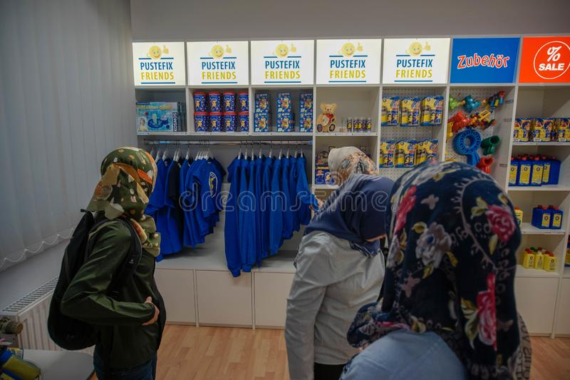 TUBINGEN/GERMANY-JULY 31 2018年:从亚洲佩带的hijab的一个回教妇女旅客在austefix商店选择杂货在城市 免版税库存图片