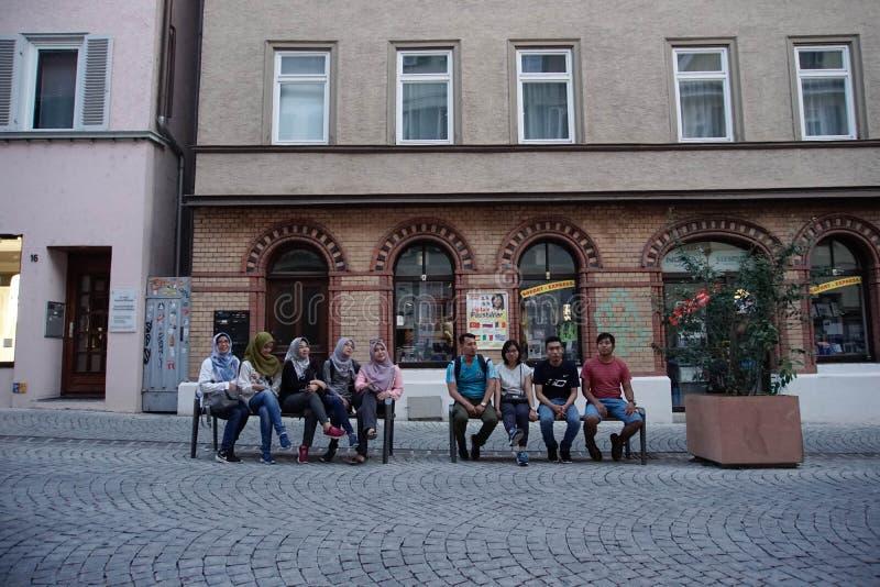 TUBINGEN/GERMANY-JULY 31 2018: några asiatiska muslimska turister sitter på en bänk nära den fot- gatan runt om staden av arkivbild