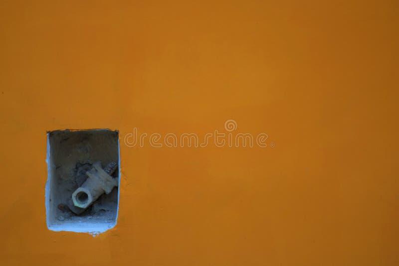 Tubo che sporge dalla parete di giallo arancio fotografia stock