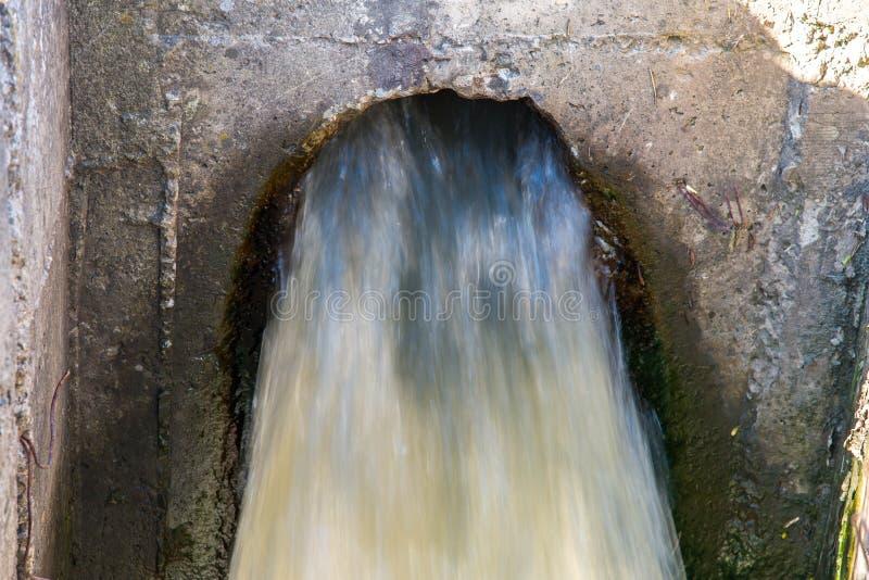 Tubo concreto que transporta el agua de aguas residuales contaminada fotografía de archivo