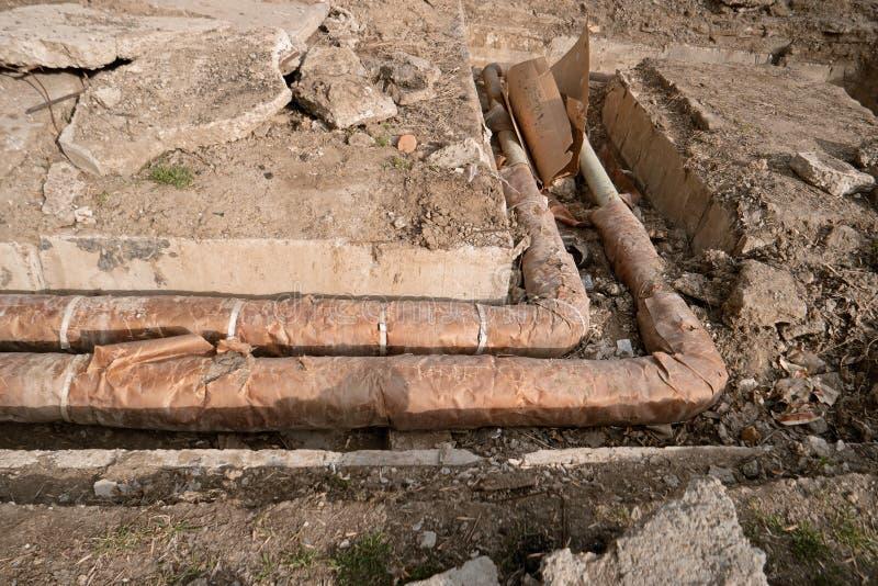 Tubo d'acciaio arrugginito con l'isolamento termico sul cantiere Riparazione del sistema a acqua caldo centrale immagini stock