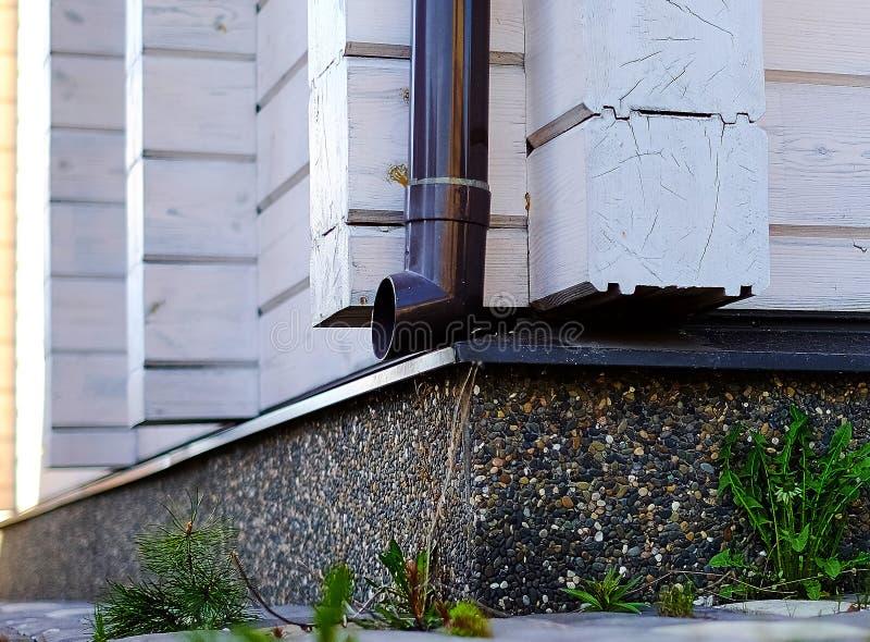 Tubo de desagüe en la pared de la casa de la madera de construcción laminada de la chapa fotos de archivo