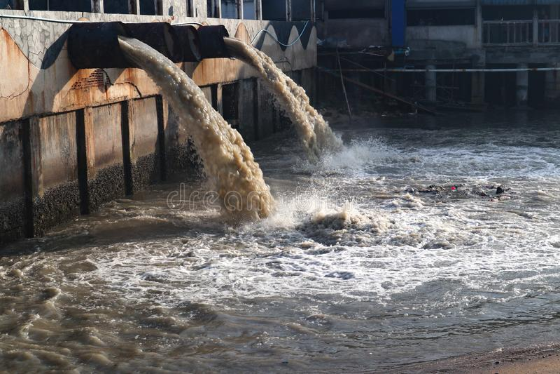 Tubo de descarga de las aguas residuales en el canal y el mar imágenes de archivo libres de regalías