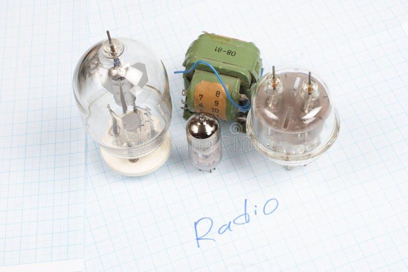 tubo de elétrons e transformador velhos do tubo de vácuo no papel de gráfico imagem de stock royalty free