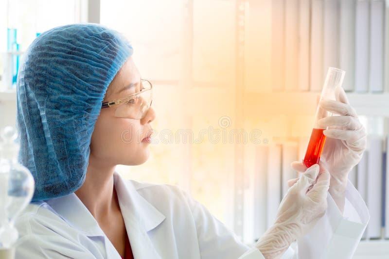 Tubo de ensayo asiático de la tenencia del científico o del químico de la mujer en el laboratorio imágenes de archivo libres de regalías