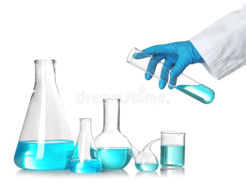 Tubo de ensayo de la tenencia del científico sobre la tabla con cristalería de laboratorio Investigaci?n qu?mica imagenes de archivo