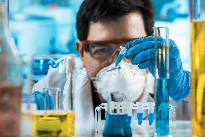 Tubo de ensayo de la tenencia del ingeniero del investigador en el laboratorio de la investigación foto de archivo libre de regalías