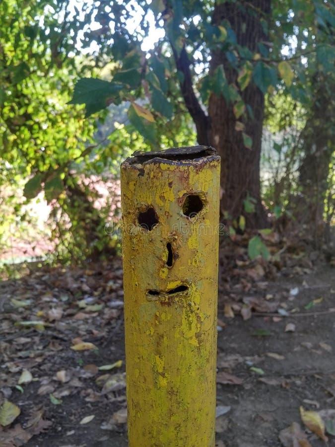 Tubo de gas amarillo parecido a un rostro humano, fondo de árboles foto de archivo
