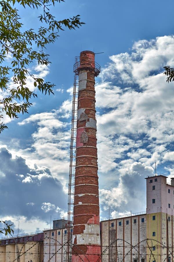 Tubo de la chimenea de la fábrica, en la planta que muele fotos de archivo