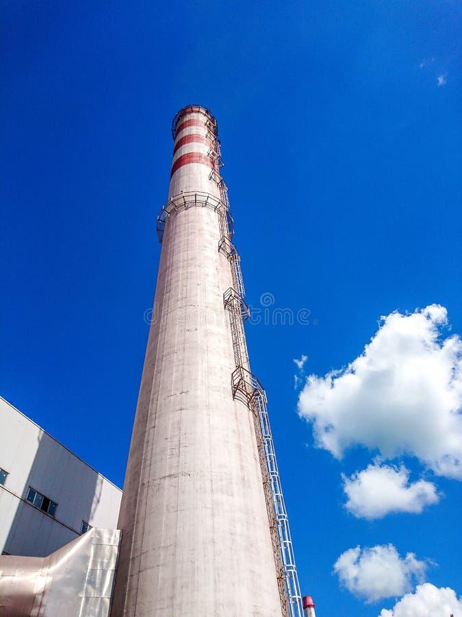 Tubo de la fábrica del ladrillo en un fondo del cielo azul con las nubes blancas Visi?n inferior El concepto de producción del li fotografía de archivo