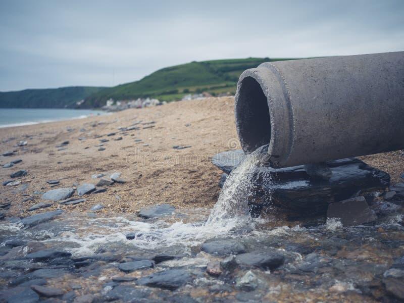 Tubo de las aguas residuales en la playa fotos de archivo libres de regalías