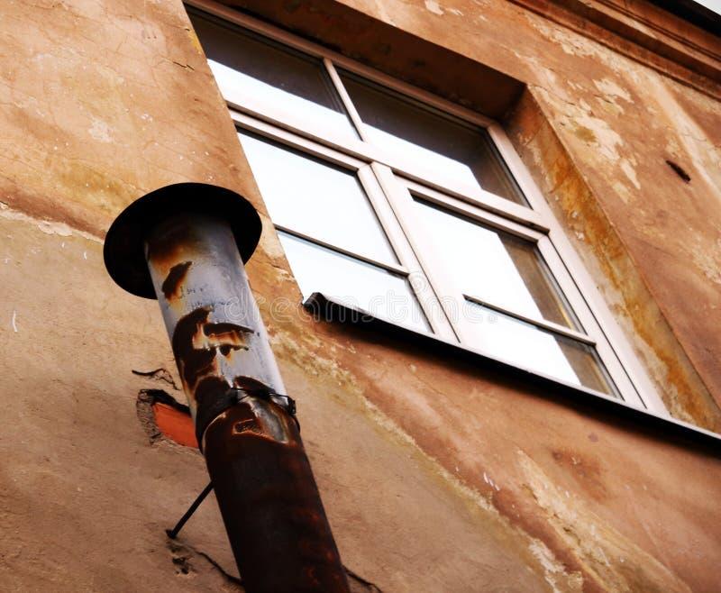 Tubo de metal da chaminé pendurado perto de uma janela de plástico fotografia de stock royalty free