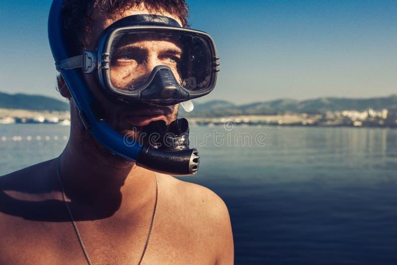Tubo de respiração masculino de With Mask And do mergulhador de mergulhador que está na praia no fundo da costa de mar imagem de stock royalty free