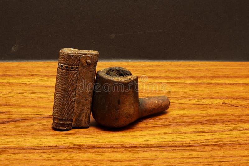 Tubo de tabaco con el encendedor fotografía de archivo libre de regalías