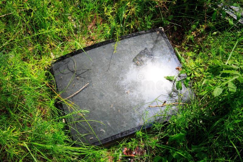 Tubo de televisión quebrado en hierba verde imagen de archivo libre de regalías