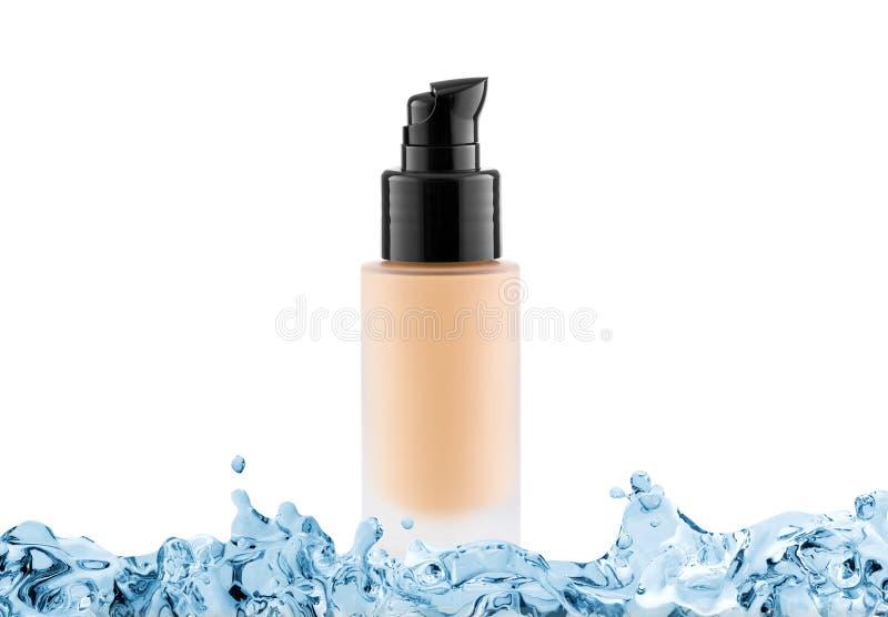 Tubo de vidro cosmético da fundação com espaço da cópia no respingo da água, creme do tom imagem de stock