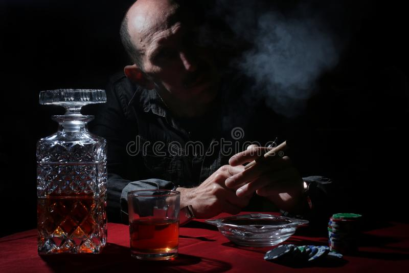 Tubo del humo del hombre y póker del juego imagen de archivo