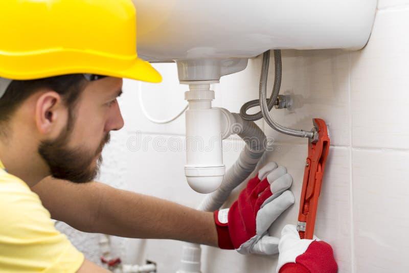 Tubo del lavandino della riparazione dell'idraulico con la chiave immagine stock libera da diritti
