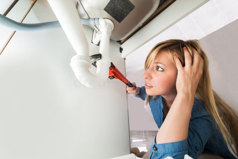 Tubo del lavandino della riparazione della donna con la chiave in cucina immagini stock