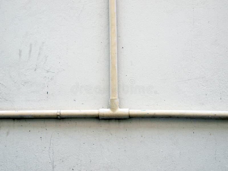 Tubo dell'impianto idraulico contro la parete dello stucco immagine stock libera da diritti